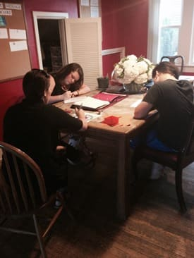 Three youth sitting at a table doing homework.