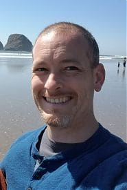 A white man smiling beach in the background.