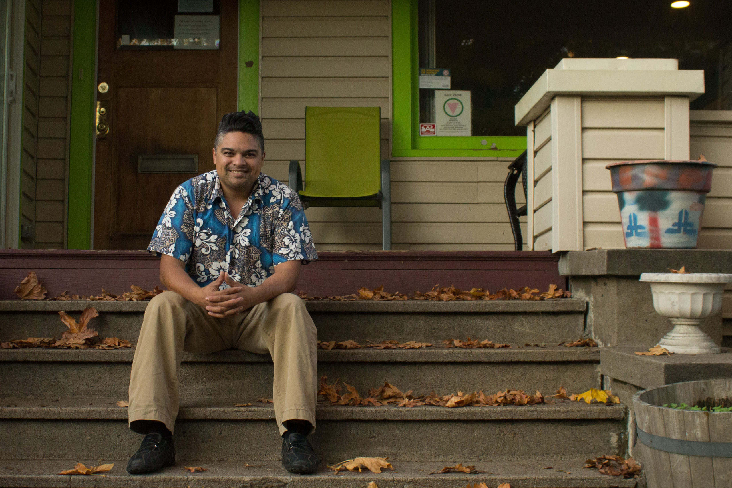 A man siting on porch steps smiling