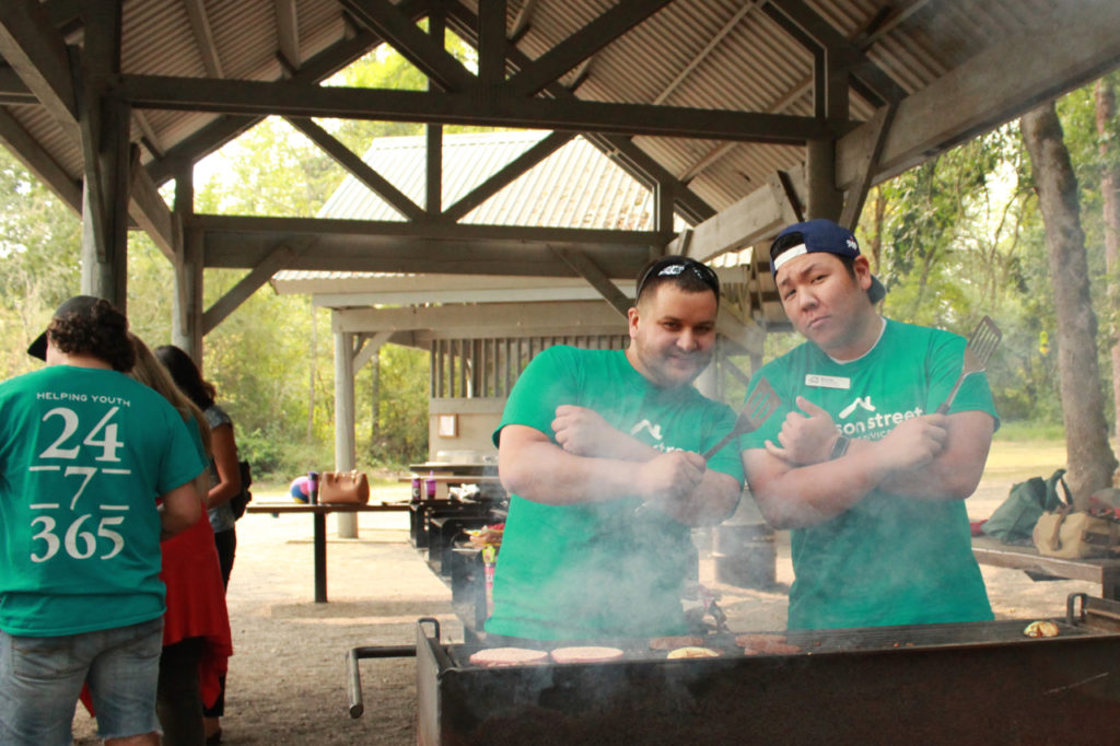 Two staff members smiling with arms folded and with spatulas over a BBQ.