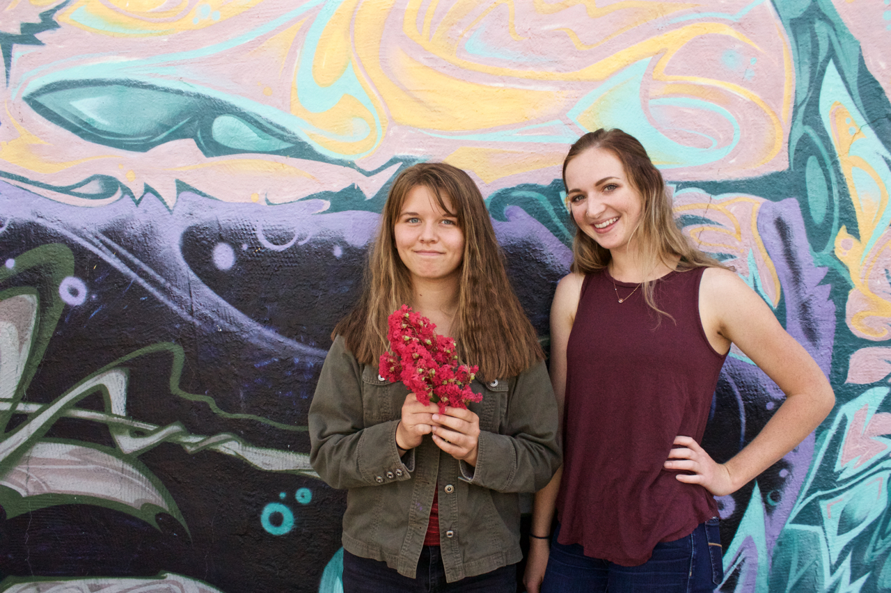 A youth and Anna smiling at a camera, a mural with bright colors in the background.