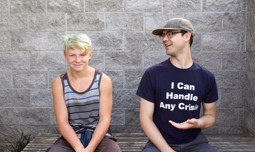 Youth on the left, staff on the right in a shirt that says I can handle any crisis. Youth is smiling while staff member is smiling at the youth.