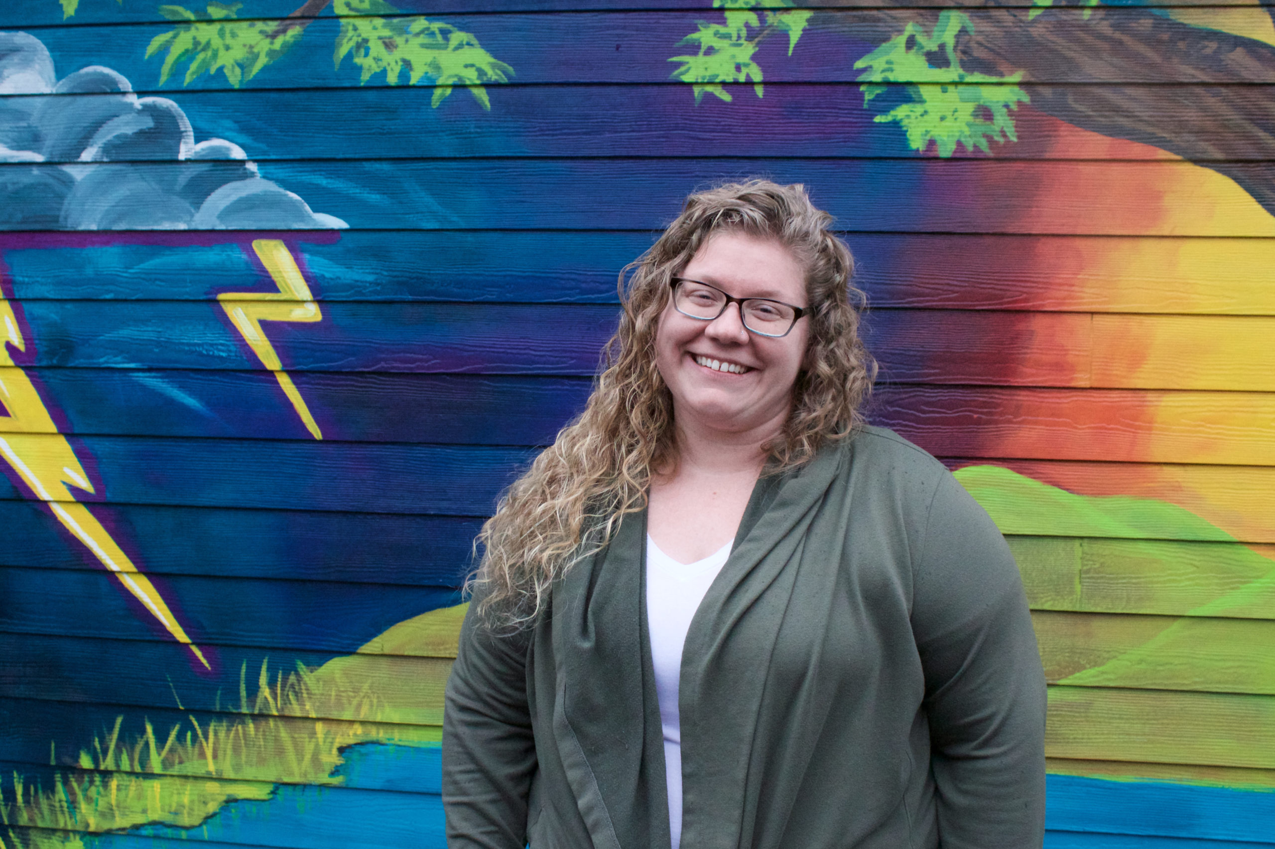 White woman in glasses smiling, a mural with bright colors is behind her.