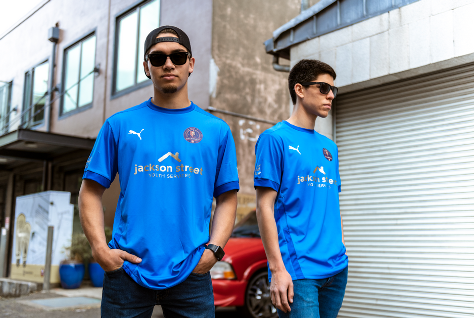 Two folks in sunglasses wearing a jersey with the Jackson Street logo on the front.